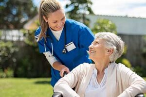 Nurse pushing smiling elderly woman in wheelchair outdoors